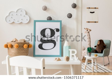 Modern and design scandinavian interior of kidroom with white desk, armachirs, mock up poster frame, natural basket, toys, teddy bear, plush toys and cute children's accessories. Stylish home decor.