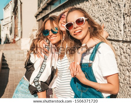 Portrait of three young beautiful smiling hipster girls in trendy summer clothes. Sexy carefree women posing on the street background.Positive models having fun in sunglasses.Shows tongue