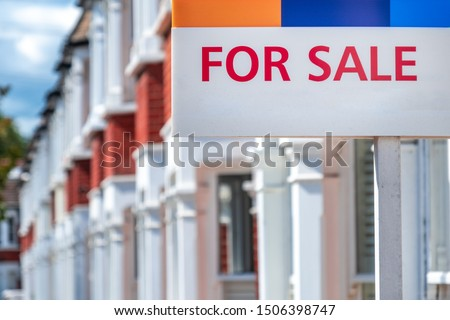 'FOR SALE' estate agency sign on street of houses