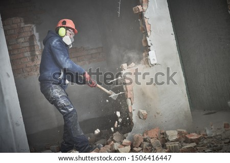 demolition work and rearrangement. worker with sledgehammer destroying wall #1506416447