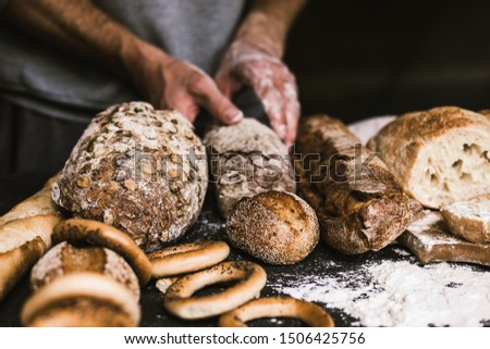 Baker man holding a rustic organic loaf of bread in his hands #1506425756