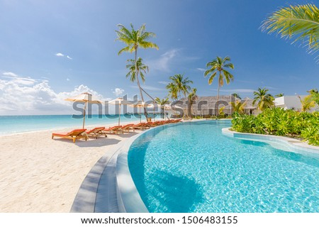 Outdoor tourism landscape. Luxurious beach resort with swimming pool and beach chairs or loungers under umbrellas with palm trees and blue sky. Summer travel and vacation background concept Royalty-Free Stock Photo #1506483155