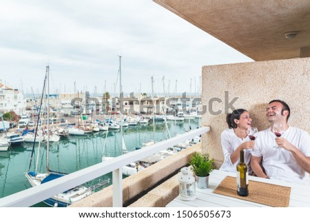 Happy  young couple smiling, drinking red wine on the terrace at the marina. Couple relationship and lifestyle concept. #1506505673