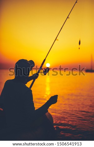 Silhouette of a fisherman fishing in sunset time on the open sea. #1506541913