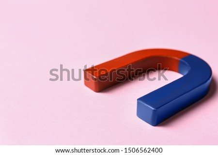 Red and blue horseshoe magnet on pink background