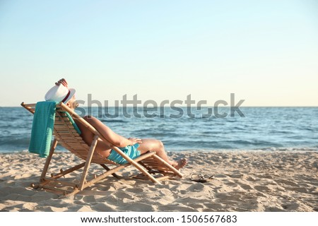 Young man relaxing in deck chair on beach near sea #1506567683