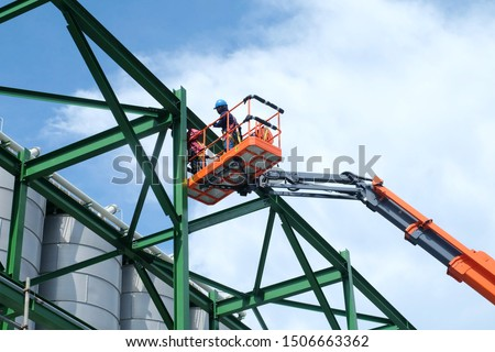 Two workers are driving the Orange articulate boom lift or telescopic boom lifts and bucket crane mounted on truck to safety for working at heights and articulating boom lift reaching high up. #1506663362