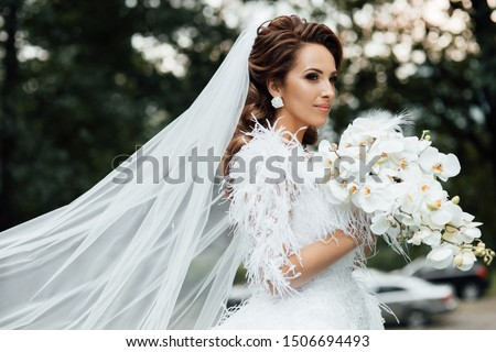 Bride holding a bouquet of white orchids. Beautiful woman. Wedding bouquet in bride's hands. Beautiful bride in white dress in the garden. Beautiful woman with professional make up and hair style. #1506694493