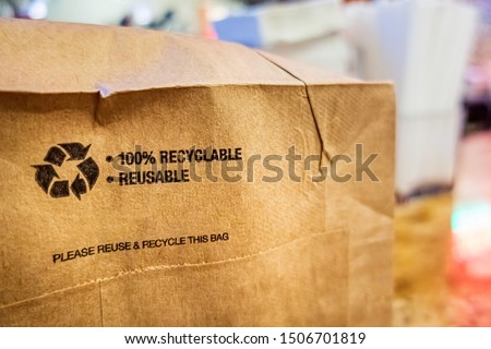 Brown paper bag that is 100% recyclable and reusable on a counter. A printed plea for user to recycle and reuse this bag as a form of packaging. Royalty-Free Stock Photo #1506701819
