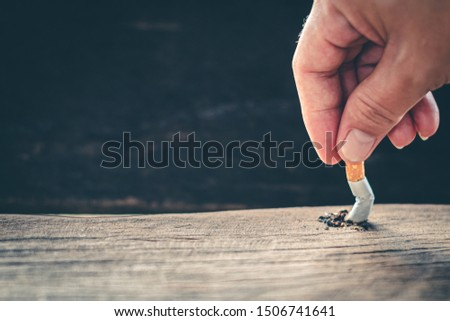 The hand held a cigarette to crush smoke of a burning, Stop smoking concept. #1506741641