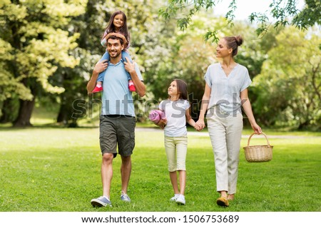 family, leisure and people concept - happy mother with picnic basket, father and two daughters walking in summer park #1506753689
