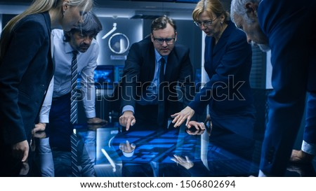 Diverse Team of Government Intelligence Agents Standing Around Digital Touch Screen Table and Tracking Suspect. FBI Agents Using Satellite Surveillance in the Dark Monitoring Room. #1506802694