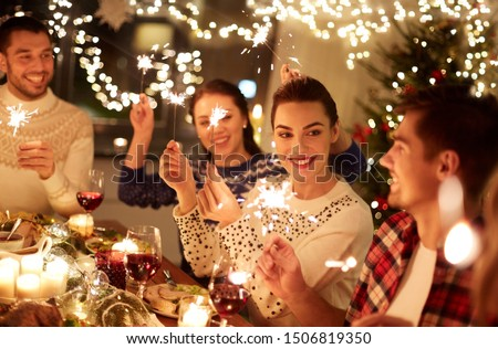 winter holidays and people concept - happy friends with sparklers celebrating christmas at home feast #1506819350