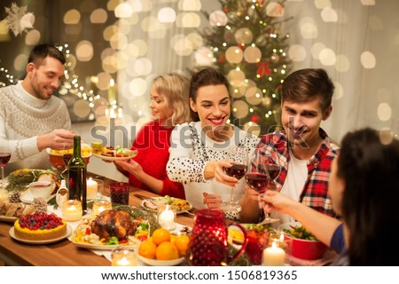 holidays and celebration concept - happy friends having christmas dinner at home, drinking red wine and clinking glasses #1506819365