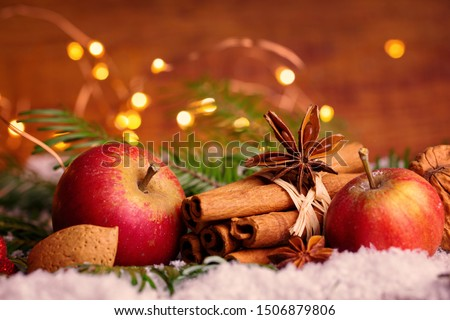 Ingredients and spices for christmas bakery   -  Almond, cinnamon sticks, apple, star anise  decorated with christmas cookie in snow #1506879806