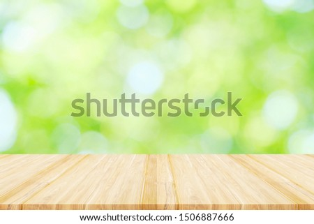 Empty wooden table or shelf with Blurred image of abstract circular green bokeh from nature background,  Ready for product display montage. #1506887666