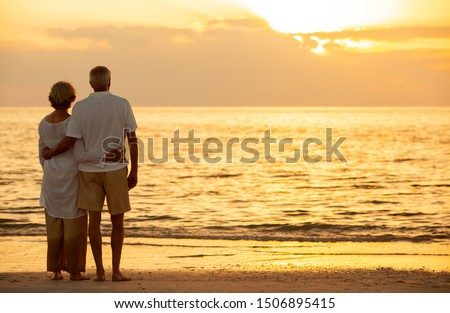 Senior man and woman couple embracing at sunset or sunrise on a deserted tropical beach  #1506895415
