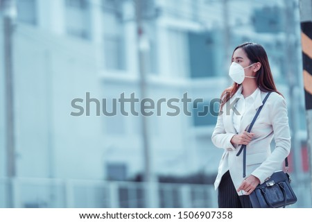 Asian woman are going to work.she wears N95 mask.prevent PM2.5 dust and smog Royalty-Free Stock Photo #1506907358