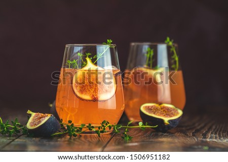 Pink cocktail with fig, thyme and ice in glass on dark wooden background, close up. Summer drinks and alcoholic cocktails. Alcoholic or detox cocktail #1506951182