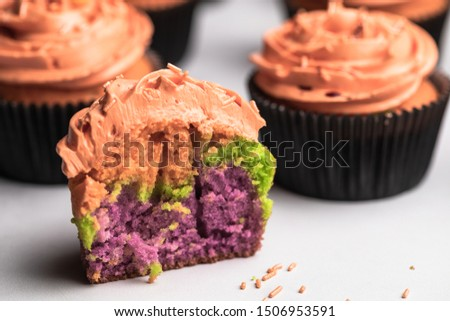 A half of a Halloween cupcake. Green and purple cupcake topped with candy corn frosting and orange frosting. #1506953591