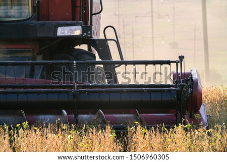 The harvest in the fields with harvester. Big harvester collects graine harvest on the field in autumn. #1506960305