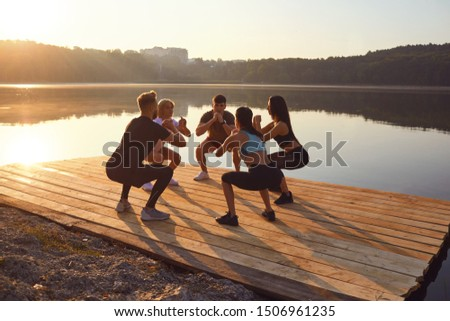 A group of sports people do squat exercises in a park by the lake #1506961235