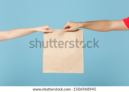 Close up cropped hands hold brown clear empty blank craft paper bag food for takeaway isolated on blue background. Packaging template mock up. Delivery service concept. Copy space. Advertising area Royalty-Free Stock Photo #1506968945