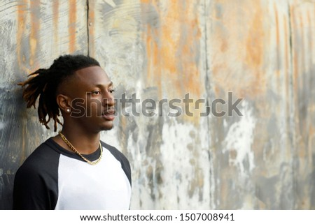 Young Handsome African American Black Male outside wearing a black and white baseball jersey henley shirt with a serious look face. Man with a profile view looking off at the future.