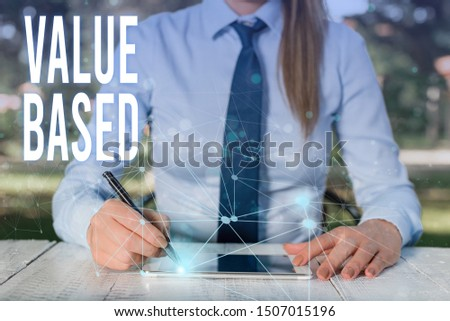 Conceptual hand writing showing Value Based. Business photo showcasing Considering the product worth in satisfying the customer Female human wear formal work suit presenting smart device. #1507015196