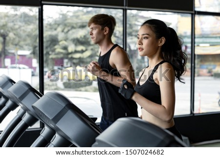 Young woman and man running side by side on modern electric treadmills at the gym. Pretty Asian woman running on treadmill with fit young man on background. Young couple on electric treadmills. #1507024682