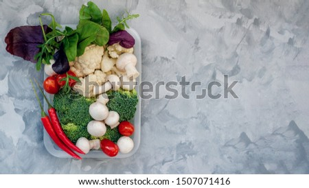 Mixed cauliflower and broccoli vegetables, baby salad, mushrooms, peppers, tomatoes and chili in lunch box on wooden background in rustic style. #1507071416