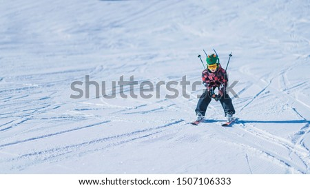 Child skiing in mountains. Active teenage kid with safety helmet, goggles and ski poles running down ski slope.  Snowy landscape, sunny day in winter season #1507106333