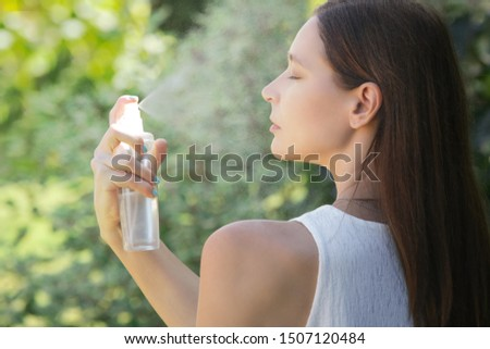 Woman spraying facial mist on her face, summertime skincare concept Royalty-Free Stock Photo #1507120484