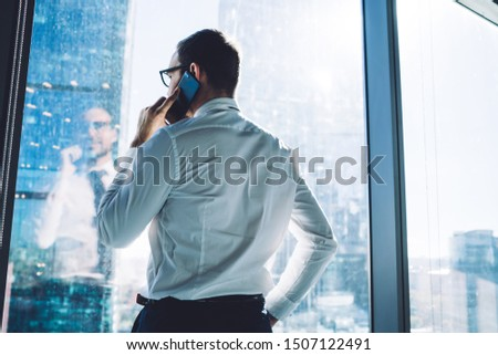 Back view of proud CEO dressed in official wear calling via mobile phone standing in office interior, male entrepreneur talking with client via cellphone during work day in enterprise corporation #1507122491