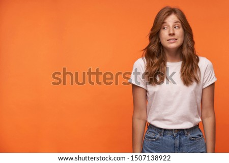Studio shot of confused young redhead woman wearing white t-shirt and blue jeans. Looking aside and contracting forehead, isolated over orange background #1507138922