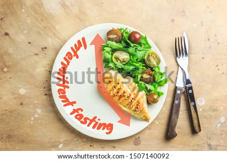 Intermittent fastin concept. One-third plate with healthy food and two-third plate is empty. Chicken fillet, arugula and tomatoes on a plate. Top view. Flat lay #1507140092