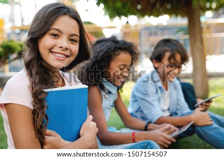 Portrait of cute little school girl and childrens on background with backpacks and notebooks outdoor Royalty-Free Stock Photo #1507154507