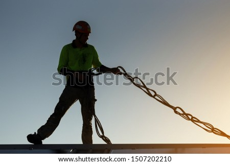 Silhouette pic of rope access construction worker wearing a safety fall protection helmet standing on top roof uncoiling twisted inspecting rope prior used construction site Sydney, Australia