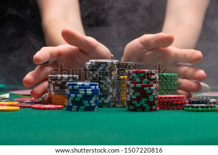 A player playing in a casino raises the bet with chips effectively with smoke. Gaming business #1507220816