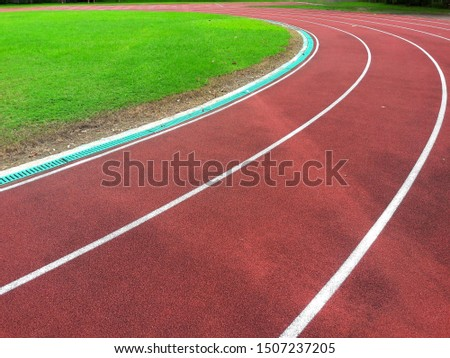 White lines of stadium and texture of running racetrack red rubber racetracks in outdoor stadium and green grass field,empty athletics stadium with track,football field, soccer field. #1507237205