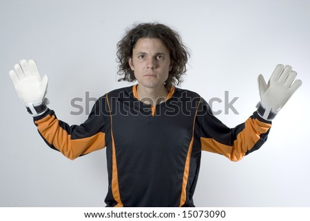 Soccer goalie wearing gloves looks serious as he has his hands out. Horizontally framed photograph. #15073090