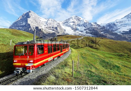 A cogwheel train travels on the railway from Jungfraujoch (top of Europe) to Kleine Scheidegg on the green grassy hillside with Eiger, Monch & Jungfrau in background in Bernese Highlands, Switzerland #1507312844