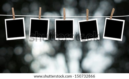 Blank photographs hanging on a clothesline against a Bokeh lights background #150732866