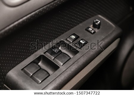 Novosibirsk, Russia – August 24, 2019:  Nissan X-trail, Close up of a door control panel in a new modern car. Arm rest with window control panel, door lock button, and mirror control. #1507347722