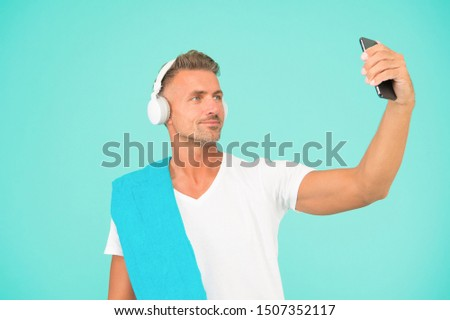 Selfie in gym concept. Sportsman smartphone and headphones. Healthy lifestyle. Gym aesthetics. Mature but still in good shape. Exercising in gym for better health. Man athlete taking selfie photo.