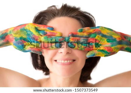 Young cheerful soiled in paint girl having fun. Smiling Woman with bright makeup isolated on White background. artistic colorful portrait of a young beautiful model with face covered with paint Royalty-Free Stock Photo #1507373549