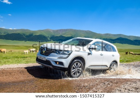 ALMATY, KAZAKHSTAN - JULY 20, 2019: Renault Koleos drives off road in Kazakstan. French SUV crosses a stream by wading. The front of the Koleos features large C-shaped LED daytime running lights. #1507415327