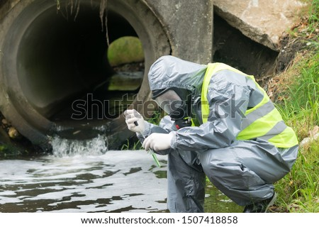 a man in a protective suit takes a sample of water from the river after the release of chemical waste #1507418858