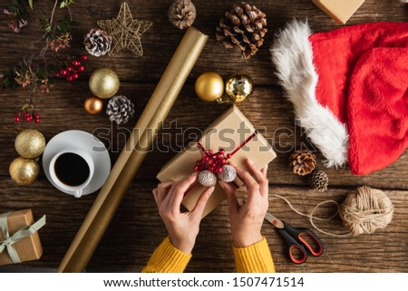 Hands wrapping christmas gifts on wooden table #1507471514