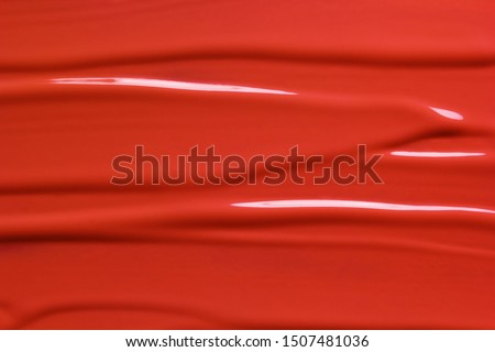 Red lipstick texture background. Beauty cosmetic product or paint sample. Liquid lipstick or lip gloss smear smudge stroke #1507481036